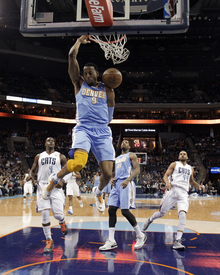 Photo - Denver Nuggets' Andre Iguodala (9) dunks as he gets in front of Charlotte Bobcats' Jeff Adrien (4), Nuggets' Wilson Chandler (21) and Bobcats' Jeffery Taylor (44) during the first half of an NBA basketball game in Charlotte, N.C., Saturday, Feb. 23, 2013. (AP Photo/Bob Leverone)