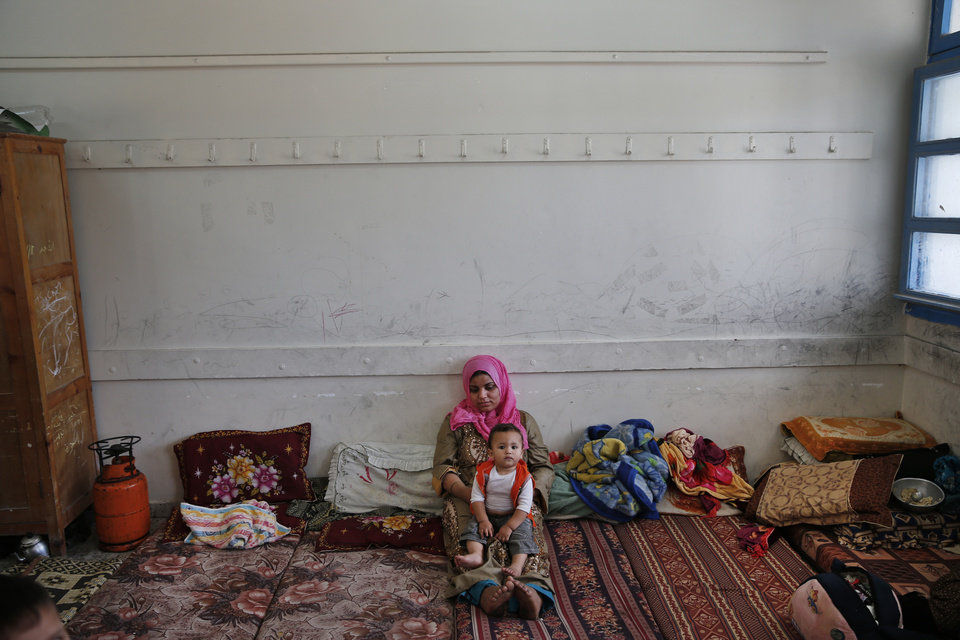 Photo - A Palestinian woman holds her baby as she sits in a classroom at a United Nations school where dozens of families have sought refuge after fleeing their homes following heavy Israeli forces' strikes in Beit Hanoun, northern Gaza Strip, Saturday, July 19, 2014. Gaza Health Ministry spokesman Ashraf al-Kidra said the new round of strikes raised the death toll from the 12-day offensive to more than 330 Palestinians, many of them civilians. (AP Photo/Lefteris Pitarakis)