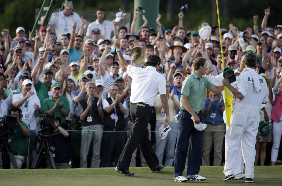 Photo - Spectators applaud Bubba Watson, left,  after winning the Masters golf tournament Sunday, April 13, 2014, in Augusta, Ga. Second right is Jordan Spieth and their caddies. (AP Photo/Darron Cummings)