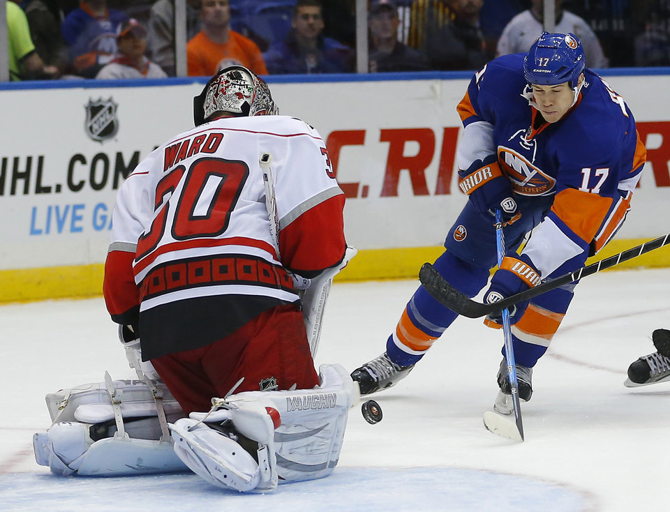 New York Islanders left wing Matt Martin (17) is stopped by Carolina Hurricanes goalie Cam Ward (30) during the second period of an NHL hockey game at the Nassau Coliseum in Uniondale, N.Y., Monday, Feb.11, 2013. (AP Photo/Paul J. Bereswill)