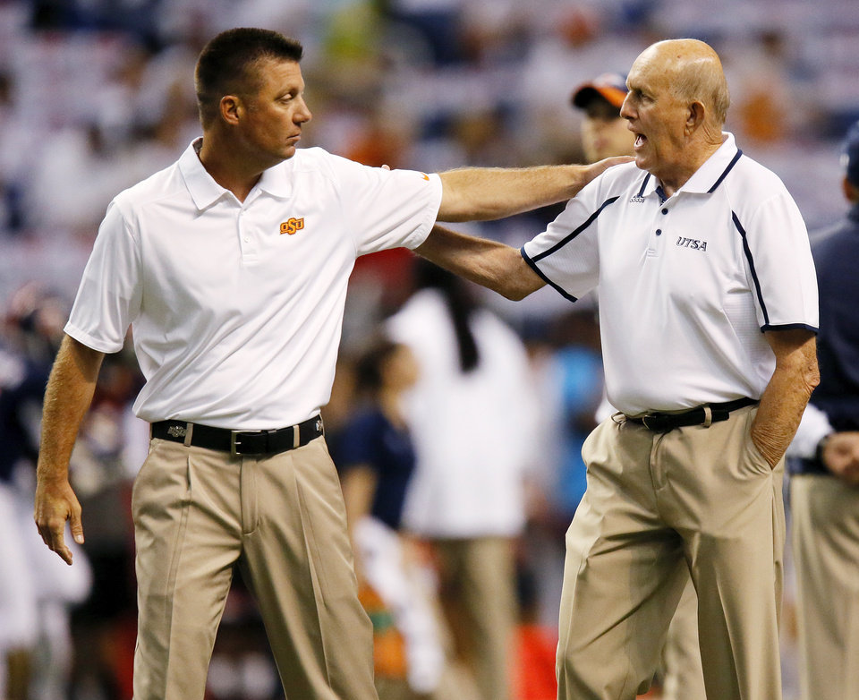 Photo - OSU head coach Mike Gundy, left, and UTSA head coach Larry Coker talk before a college football game between the University of Texas at San Antonio Roadrunners (UTSA) and the Oklahoma State University Cowboys (OSU) at the Alamodome in San Antonio, Saturday, Sept. 7, 2013.  Photo by Nate Billings, The Oklahoman