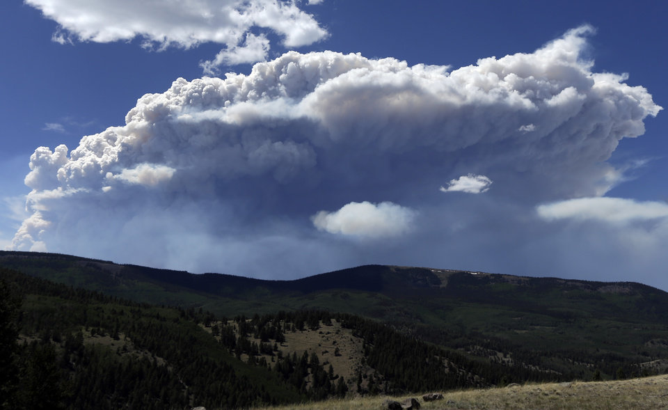 Photo - Wildfire smoke plumes above Del Norte Peak on Sunday, June 23, 2013, in near Del Norte, Colo. A large wildfire near a popular summer retreat in southern Colorado continues to be driven by winds and fueled by dead trees in a drought-stricken area, authorities said Sunday. (AP Photo/Gregory Bull)