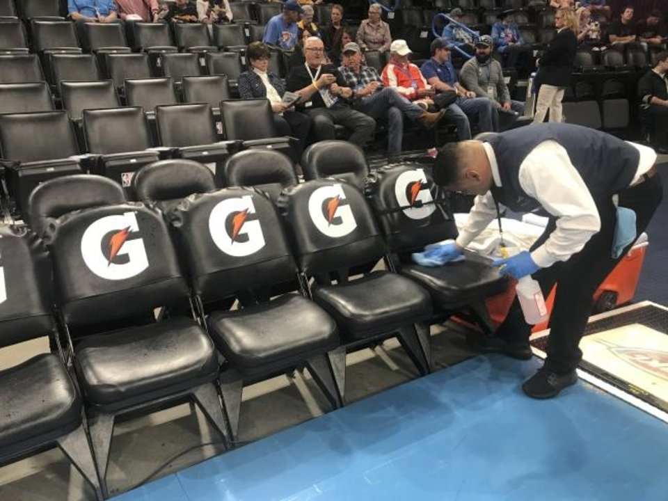 Photo -  A worker cleans the Oklahoma City Thunder bench seats before an NBA basketball game between the Oklahoma City Thunder and the Utah Jazz at Chesapeake Energy Arena in Oklahoma City, Wednesday, March 11, 2020. [Bryan Terry/The Oklahoman]
