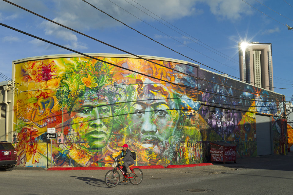 Photo - This July 12, 2014 photo shows a bicyclist riding past a mural depicting the portraits of Hawaiian Queen Liliuokalani and King David Kalakaua, in Honolulu.  The urban art piece is a collaboration between Native Hawaiian artists Solomon Enos and John