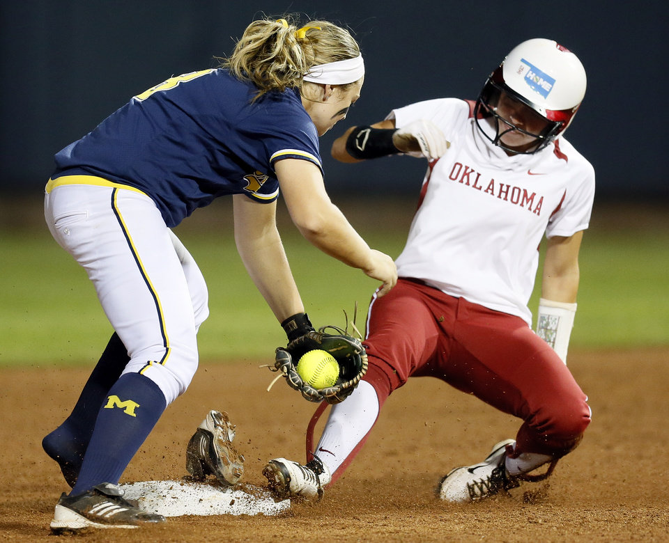 Photo - OU's Destinee Martinez (00) makes it safely to second base as Michigan's Ashley Lane (8) loses her shoe in the second inning during an NCAA softball game in the Women's College World Series between Oklahoma and Michigan at ASA Hall of Fame Stadium, Thursday, May 30, 2013. Photo by Nate Billings, The Oklahoman