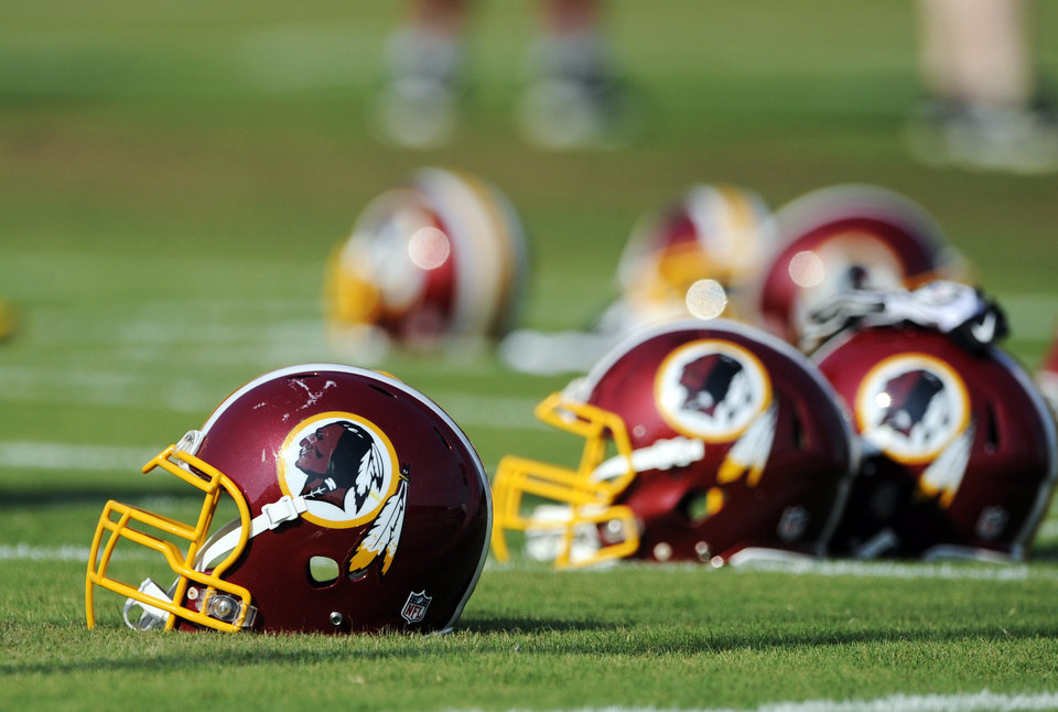 Photo - FILE - In this June 17, 2014, file photo, Washington Redskins helmets sit on the field during an NFL football minicamp in Ashburn, Va. The U.S. Patent Office ruled Wednesday, June 18, 2014, that the Washington Redskins nickname is
