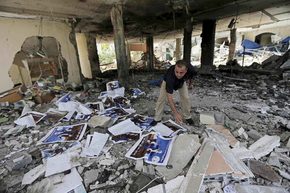 Photo - A Palestinian searches the rubble of a center for disabled, that is littered with posters soliciting donations to support the Al Mabara association for handicapped run by Hamas, after an Israeli missile strike in Beit Lahiya, in the northern Gaza Strip, Saturday, July 12, 2014. Israeli airstrikes on Gaza hit a mosque and a center for the disabled where two women were killed Saturday, raising the Palestinian death toll from the offensive to more than 125, Palestinian officials said, in an offensive that showed no signs of slowing down. (AP Photo/Adel Hana)