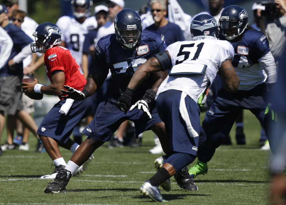Seattle Seahawks tackle Russell Okung (OSU), center, squares off against defensive end Bruce Irvin (51) to protect quarterback Russell Wilson, left, during NFL football training camp, Saturday, July 27, 2013, in Renton, Wash. (AP Photo/Ted S. Warren)