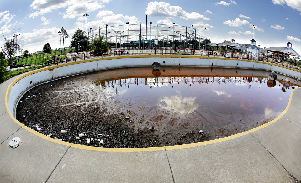 Photo -  An abandoned bumper boats pool sits full of dirt and trash at Perfect Swing.    Jim Beckel -  THE OKLAHOMAN