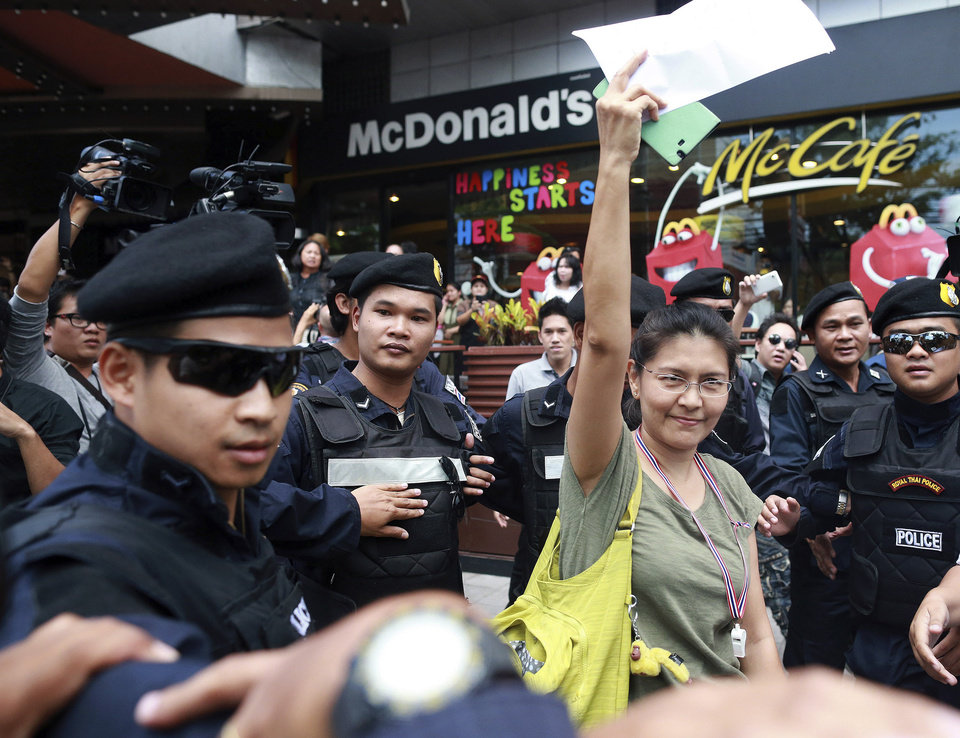 Photo - Surrounded by Thai police officers for her security, a Thai woman supporter of the coup raises arm opposing the protesters against the coup outside a shopping complex in Bangkok, Thailand Saturday, May 24, 2014. Thailand's coup leaders said Saturday they will keep former Prime Minister Yingluck Shinawatra, Cabinet members and anti-government protest leaders detained for up to a week to give them