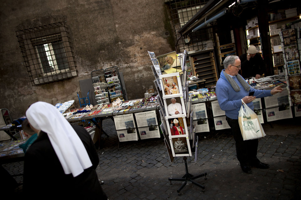 Photo - A man looks at postcards of Pope Benedict XVI, just outside St. Peter's Square, a day before the Pope last general audience, scheduled for Wednesday, at the Vatican, Tuesday, Feb. 26, 2013. Pope Benedict XVI will be known as