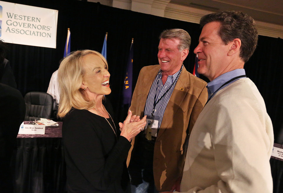 Photo - Governor of Arizona Jan Brewer, left, talks with fellow Governors Sam Brownback of Kansas, right, and Idaho's Butch Otter, during the annual Western Governors' Association Meeting, at the Broadmoor Hotel in Colorado Springs, Tuesday, June 10, 2014. Ten governors from western states attended the second day of the conference Tuesday, discussing common regional issues. (AP Photo/Brennan Linsley)