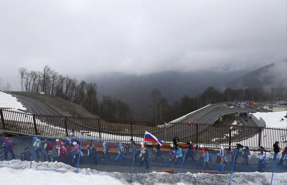 Photo - Spectators leave the venue after the men's snowboard cross competition was cancelled due to fog at the Rosa Khutor Extreme Park, at the 2014 Winter Olympics, Monday, Feb. 17, 2014, in Krasnaya Polyana, Russia. (AP Photo/Sergei Grits)