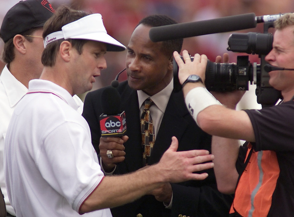 Photo - OU vs Nebraska football. OU coach Bob Stoops talks with Lynn Swann at the half as he leaves the field.