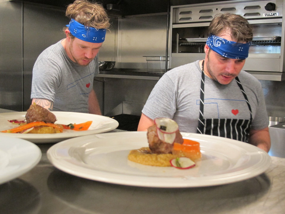 Photo - Chefs Jonathon Stranger, left, and David Henry work the line during Sunday's portion of the OK Chefs Relief Pop-Up Restaurant in the Myriad Botanicals Gardens event space. All proceeds were donated to the Oklahoma Chapter of the American Red Cross.  DAVE CATHEY - THE OKLAHOMAN