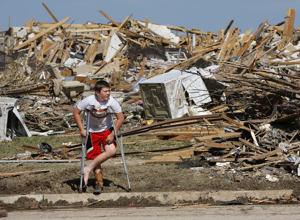 Dakota Mauk, 12, stands in front of his grandmother\'s destroyed home near SW 148 and S. Hudson in the Westmoor (cq) neighborhood on Wednesday afternoon, May 22, 2013. Mauk is on crutches after injuring his leg last night playing baseball. Photo by Jim Beckel, The Oklahoman.