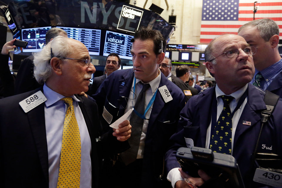 Photo - Traders Peter Tuchman, Gregory Rowe, and Frederick Reimer, left to right, work on the floor of the New York Stock Exchange, Wednesday, June 18, 2014. U.S. stocks are little changed in early trading as investors wait for the latest policy action from the Federal Reserve. (AP Photo/Richard Drew)