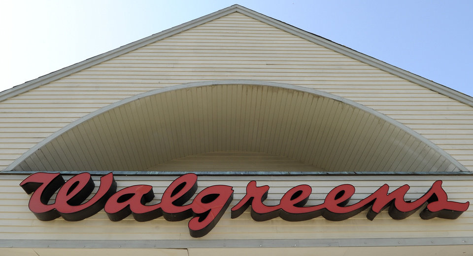FILE - Sign above a Walgreens entrance, is seen in this, Sept. 28, 2009 file photo taken in Gloucester, Mass. The nation\'s largest drugstore chain says it will buy the remaining stake in Alliance Boots that it does not already own, but it will not pull off an inversion with the Swiss health and beauty retailer. (AP Photo/Lisa Poole, File)