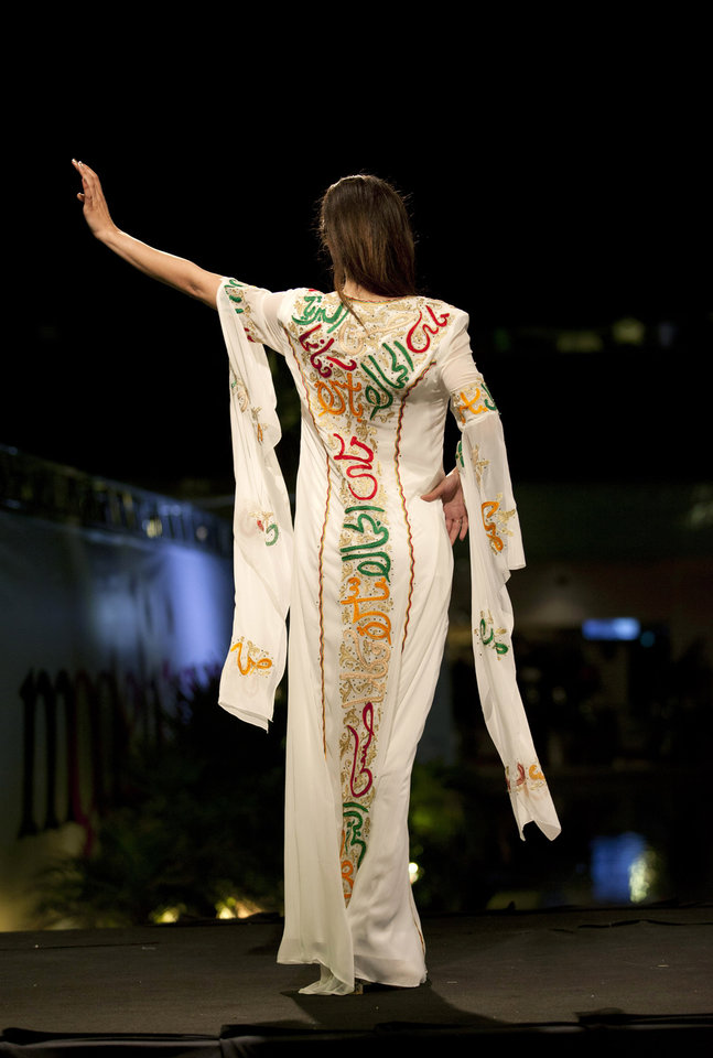 "Photo - In this photo taken Friday, May 2, 2014, a model displays a creation with embroidered Arabic calligraphy by Jordanian-Palestinian designer Intisar Abdo during the second day of the Palestine Fashion Week 2014, in the West Bank city of Ramallah. Tamer Halabi, an organizer of the event, said the show in part shows that ""we Palestinians exist."" and ""We are surviving, we have talents, we have designers, and we can compete with world fashion houses."