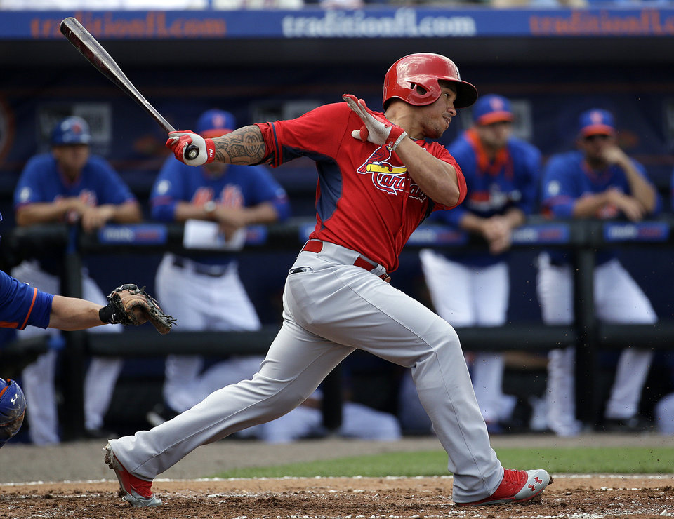 Photo - St. Louis Cardinals' Kolten Wong hits a single in the second inning of an exhibition spring training baseball game against the New York Mets, Wednesday, March 12, 2014, in Port St. Lucie, Fla. (AP Photo/David Goldman)