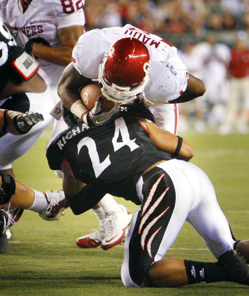 Photo - Mossis Madu (17) runs over Wesley Richardson (24) for a score during the second half of the college football game between the University of Oklahoma Sooners (OU) and the University of Cincinnati Bearcats (UC) at Paul Brown Stadium on Saturday, Sept. 25, 2010, in Cincinnati, Ohio.   Photo by Steve Sisney, The Oklahoman