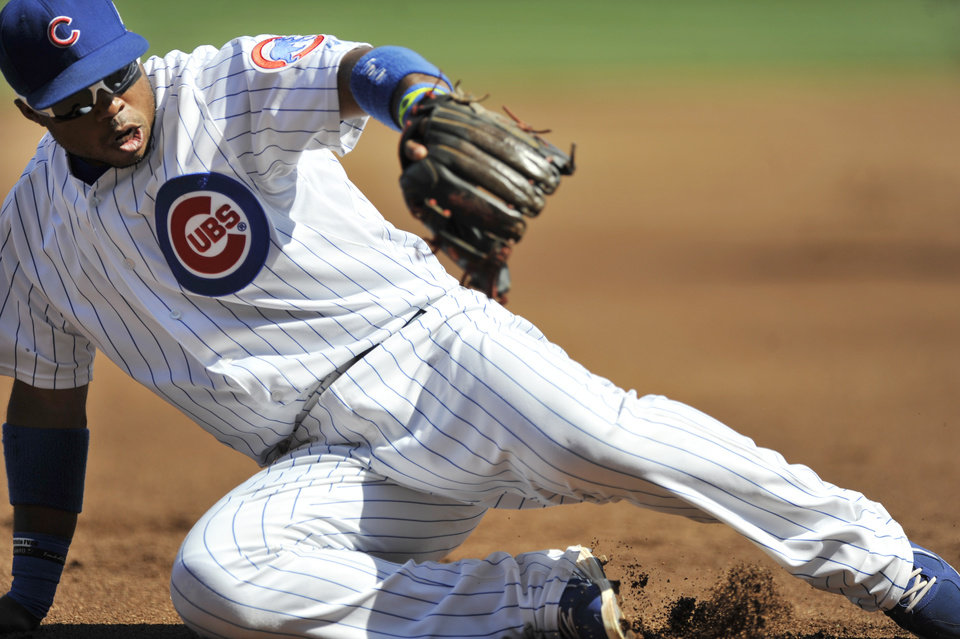Photo - Chicago Cubs third baseman Luis Valbuena stops a grounder hit by Milwaukee Brewers' Ryan Braun during the first inning of a baseball game in Chicago, Monday, Sept. 1, 2014. (AP Photo/Paul Beaty)