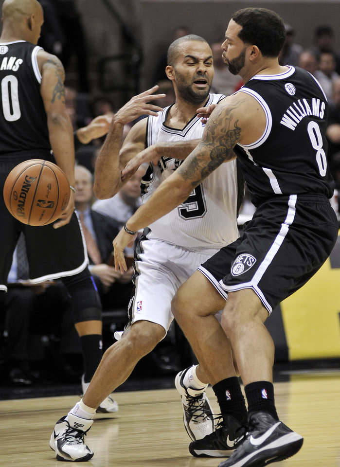 Photo - San Antonio Spurs' Tony Parker, center, of France, is defended by Brooklyn Nets' Deron Williams during the first half of an NBA basketball game, Monday, Dec. 31, 2012, in San Antonio. (AP Photo/Darren Abate)