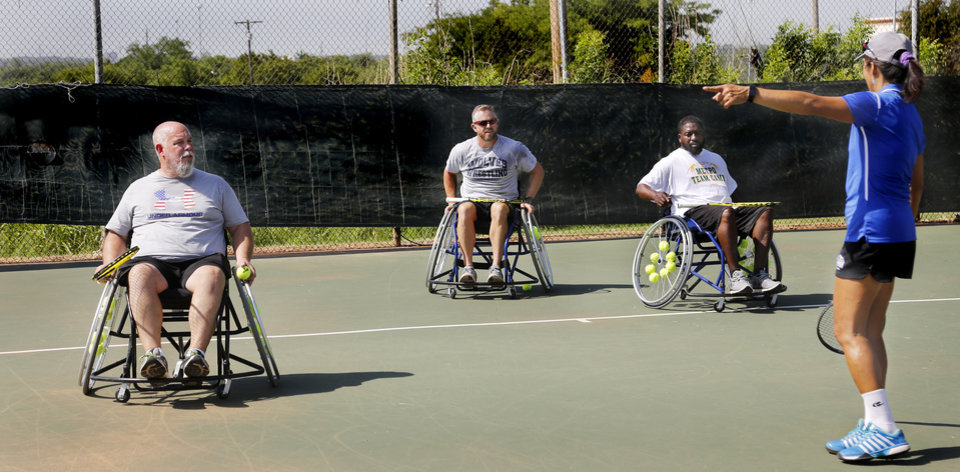 Photo -  Tennis pro Jenny Marcos directs Paul Horton, left, Brandon Taber and Tony Batchelor during a veteran's wheelchair tennis clinic at Santa Fe Family Life Center. [PHOTO BY JIM BECKEL, THE OKLAHOMAN]