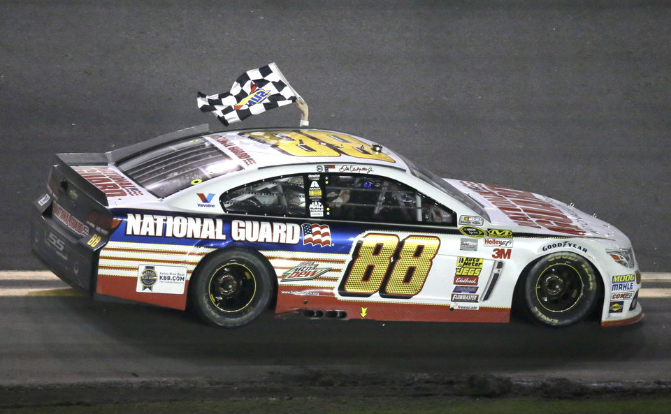 Photo - Dale Earnhardt Jr. drives in front of fans in the grandstands waving the checkered flag after winning the Daytona 500 NASCAR Sprint Cup Series auto race at Daytona International Speedway in Daytona Beach, Fla., Sunday, Feb. 23, 2014. (AP Photo/John Raoux)