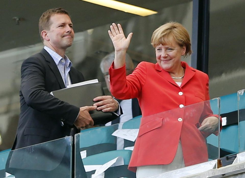 Photo - German President Angela Merkel waves after watching the group G World Cup soccer match between Germany and Portugal at the Arena Fonte Nova in Salvador, Brazil, Monday, June 16, 2014.  Germany won 4-0. (AP Photo/Matthias Schrader)
