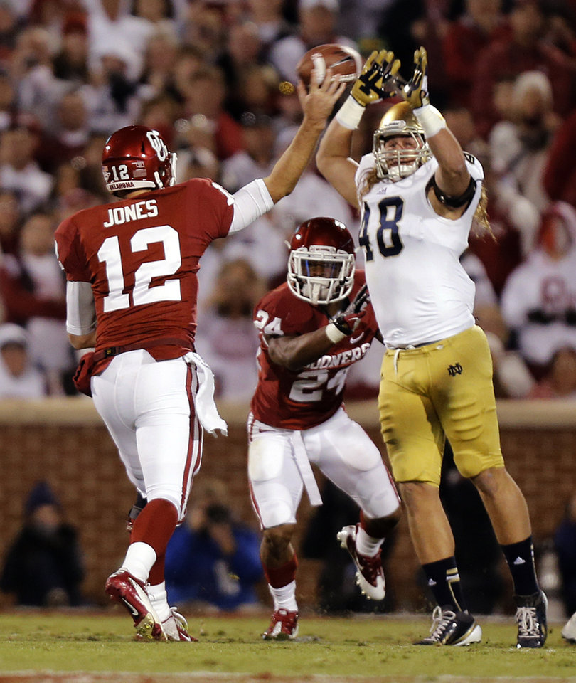 Photo - Notre Dame 's Dan Fox (48) puts pressure on OU's Landry Jones (12) during the college football game between the University of Oklahoma Sooners (OU) and the Notre Dame Fighting Irish at the Gaylord Family-Oklahoma Memorial Stadium on Saturday, Oct. 27, 2012, in Norman, Okla. Photo by Chris Landsberger, The Oklahoman