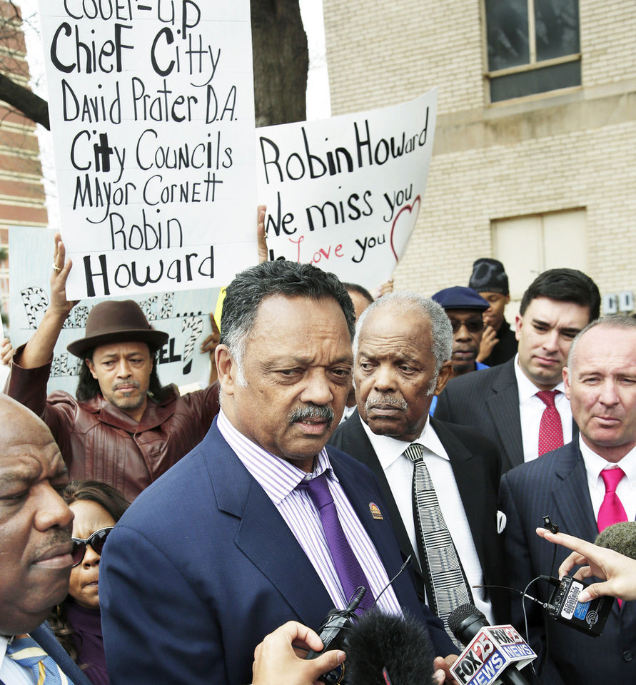 Photo - Rev. Jesse Jackson, center,  joined local pastors and clivil rights leaders in a march in downtown Oklahoma City to voice their concern about what they say is a lack of information released by Police Chief Bill Citty regarding the  death of Robin Howard, who died while in police custody in June, 2012.  Family members of  Howard were among the more than 100 people who peacefully marched Tuesday afternoon, March 19, 2013,  from Oklahoma City police headquarters to the east side of City Hall where Jackson assured the marchers he would not relent keeping pressure on the police department and its chief to find answers about Howard's death. At far left is Rev. Major Jemison,  senior pastor of St. John Missionary Baptist Church. Standing next to Jackson at right is Rev. John A. Reed, Jr., senior pastor of Fairview Missionary Baptist Church. Next to him is Brady Henderson, legal director of American Civil Liberties Union of Oklahoma. At far right is David Slane, attorney for the Howard family.    Photo by Jim Beckel, The Oklahoman