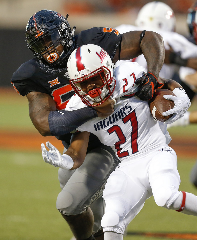 Photo - Oklahoma State's Enoch Smith Jr. (56) tackles South Alabama's Maurice Mayo (27) during a college football game between Oklahoma State (OSU) and South Alabama at Boone Pickens Stadium in Stillwater, Okla., Saturday, Sept. 8, 2018. Photo by Nate Billings, The Oklahoman
