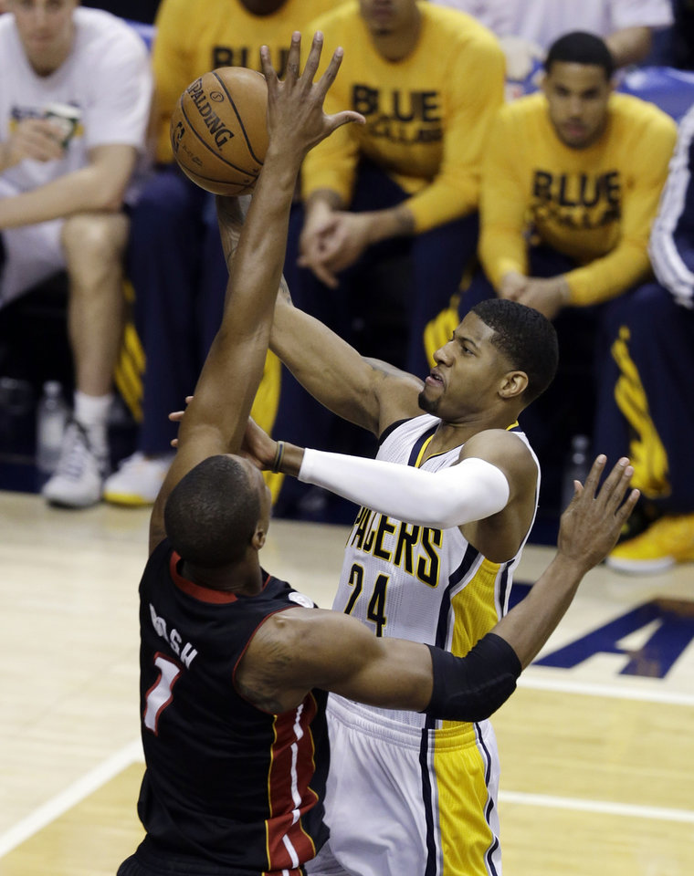 Photo - Indiana Pacers' Paul George puts up a shot against Miami Heat's Chris Bosh, left, during the first half of Game 3 of the NBA Eastern Conference basketball finals, Sunday, May 26, 2013, in Indianapolis. (AP Photo/Michael Conroy)