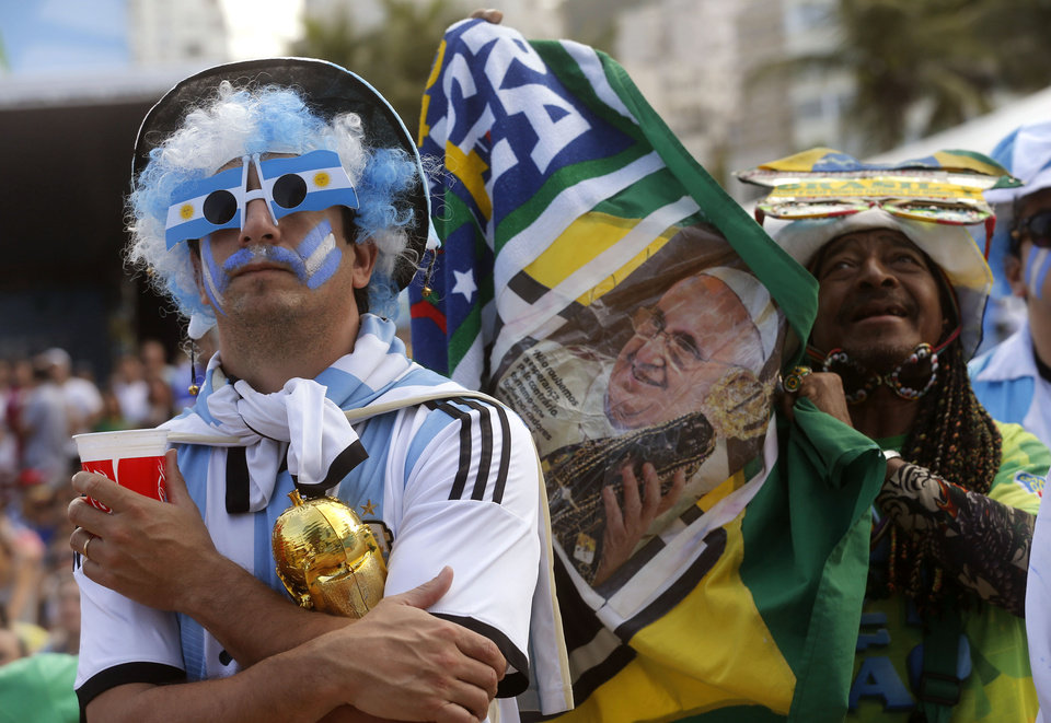 Photo - An Argentina soccer fan watches his team's World Cup match with Iran as another fan holds up a photo of Pope Francis inside the FIFA Fan Fest area on Copacabana beach, in Rio de Janeiro, Brazil, Saturday, June 21, 2014. Argentina won 1-0. (AP Photo/Silvia Izquierdo)