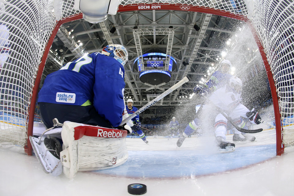 Photo - Slovenia goaltender Luka Gracnar looks back at the puck after USA forward Phil Kessel scored period of a men's ice hockey game at the 2014 Winter Olympics, Sunday, Feb. 16, 2014, in Sochi, Russia. (AP Photo/Martin Rose, Getty Images Pool)