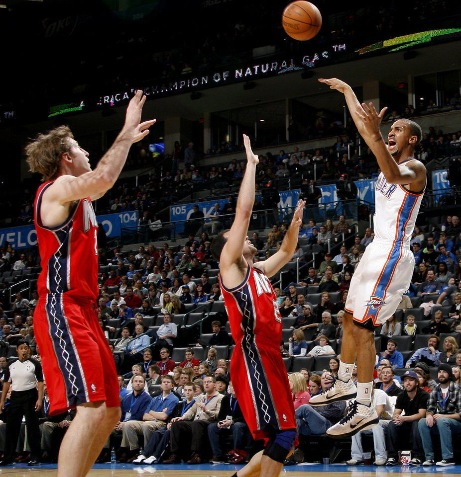 Photo - Oklahoma City's Eric Maynor passes the ball over New Jersey's Troy Murphy, left, and Jordan Farmar during the NBA basketball game between the Oklahoma City Thunder and the New Jersey Nets at the Oklahoma City Arena, Wednesday, Dec. 29, 2010.  Photo by Bryan Terry, The Oklahoman