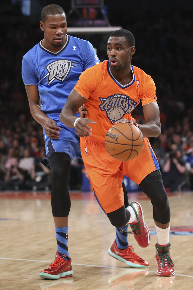 Photo - New York Knicks guard Tim Hardaway Jr. dribbles past Oklahoma City Thunder forward Kevin Durantduring the first half of an NBA basketball game at Madison Square Garden, Wednesday, Dec. 25, 2013, in New York. (AP Photo/John Minchillo)