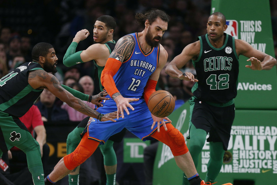 Photo - Oklahoma City Thunder's Steven Adams (12) struggles to control the ball as Boston Celtics' Kyrie Irving (11) and Al Horford (42) defend during the first half of an NBA basketball game in Boston, Sunday, Feb. 3, 2019. (AP Photo/Michael Dwyer)