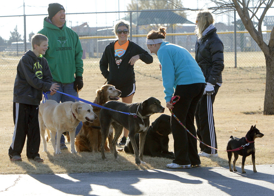 Photo - Dogs and their owners participate in the Doggie Dash 5k run at J.L. Mitch Park in Edmond. The event was a fundraiser created by a woman who is going to India to teach orphans. PHOTO BY PAUL HELLSTERN, THE OKLAHOMAN.  PAUL HELLSTERN - THE OKLAHOMAN