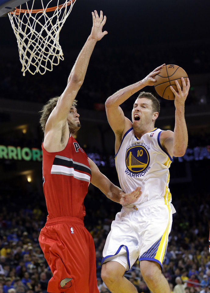 Photo - Golden State Warriors' David Lee drives to the basket as Portland Trail Blazers' Robin Lopez defends during the second half of an NBA basketball game on Sunday, Jan. 26, 2014, in Oakland, Calif. Golden State won 103-88. (AP Photo/Marcio Jose Sanchez)