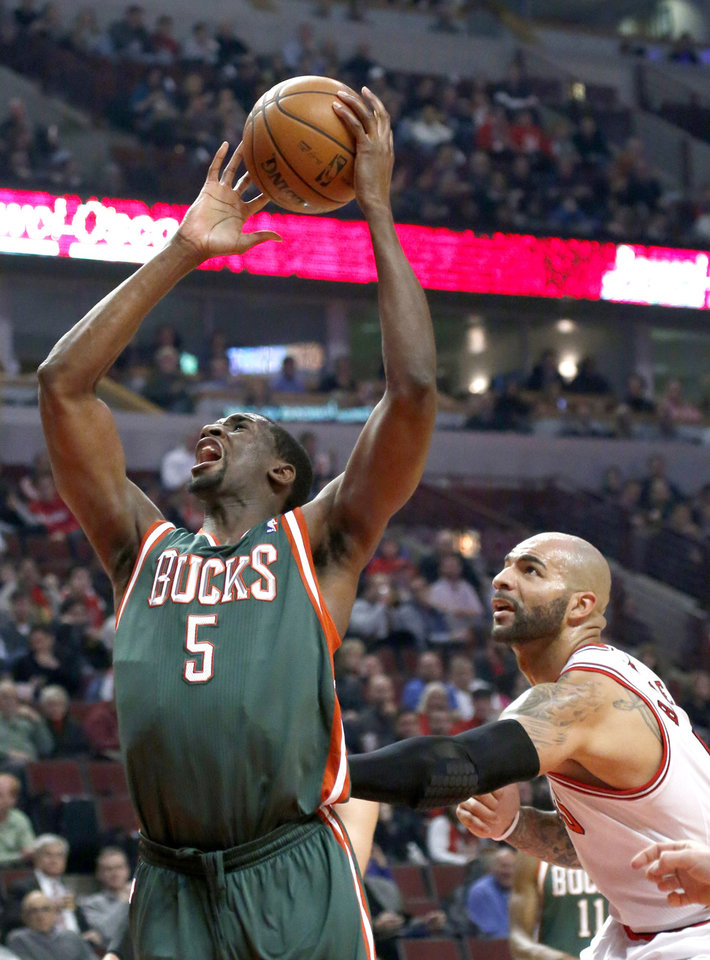 Photo - Milwaukee Bucks forward Ekpe Udoh (5) is fouled from behind by Chicago Bulls forward Carlos Boozer during the first half of an NBA basketball game Tuesday, Dec. 10, 2013, in Chicago. (AP Photo/Charles Rex Arbogast)