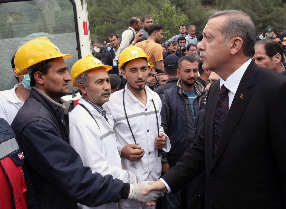 Photo - In this photo released by the Turkish Prime Minister's Press Office, Turkish Prime Minister Recep Tayyip Erdogan is surrounded by security members as he visits the coal mine in Soma, Turkey, Wednesday, May 14, 2014.  Nearly 450 miners were rescued, the mining company said, but the fate of an unknown number of others remained unclear as bodies are still being brought to the surface and burials are underway after one of the world's deadliest mining disasters. (AP Photo/Kayhan Ozer, Turkish Prime Minister's Press Office, HO)