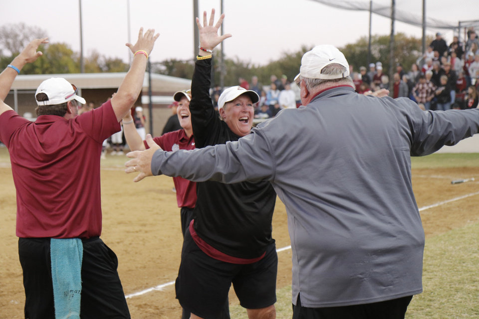 Photo - Edmond head coach Janet Chartney goes to embrace assistant coach Marcus Altstatt during the 6A Fast Pitch Championship game between Edmond Memorial and Owasso at the Ball Fields at Firelake in Shawnee, Saturday, October 19, 2019. [Doug Hoke/The Oklahoman]