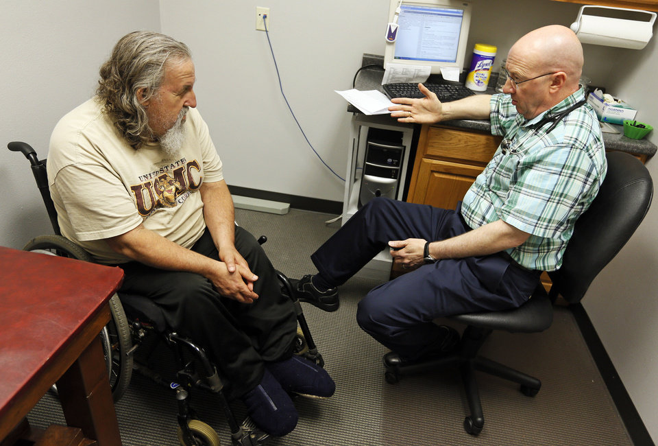 Photo - Stanley Hopkins, left, of Howe, OK, talks with Dr. Dennis Carter during an appointment at Carter's office in Poteau on June 13. Hopkins has been a patient of Carter's for more than 10 years. Photo by Nate Billings, The Oklahoman  NATE BILLINGS - NATE BILLINGS
