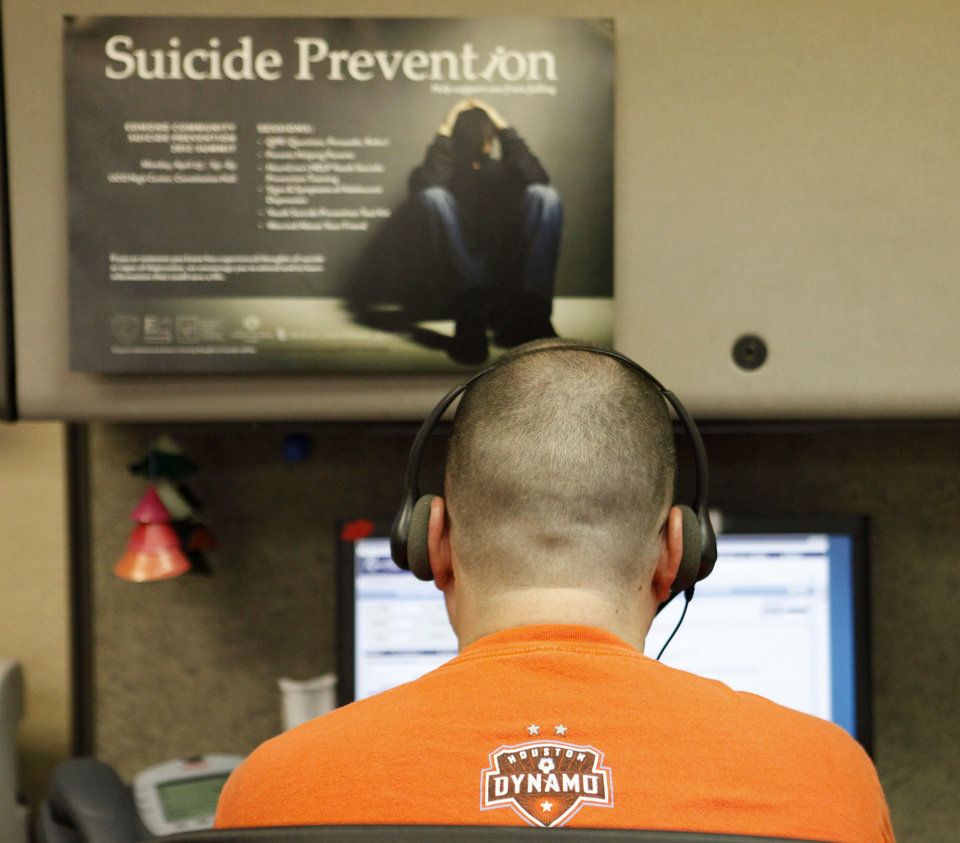 Photo - A call specialist works the phones at the Lifeline suicide prevention hotline  Steve Gooch