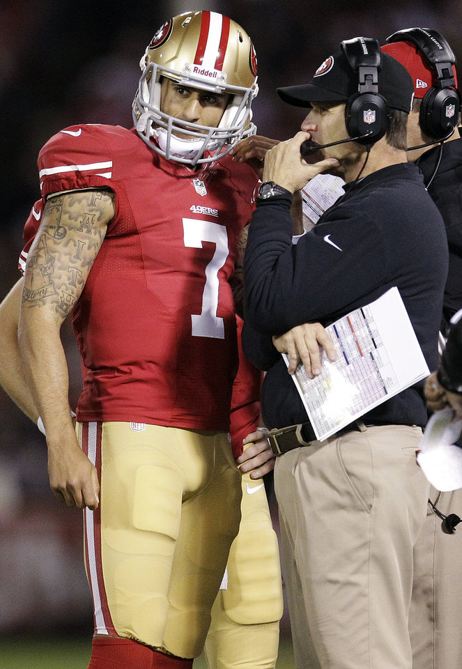 Photo -   San Francisco 49ers quarterback Colin Kaepernick (7) talks with head coach Jim Harbaugh during the first half of an NFL football game against the Chicago Bears in San Francisco, Monday, Nov. 19, 2012. (AP Photo/Tony Avelar)
