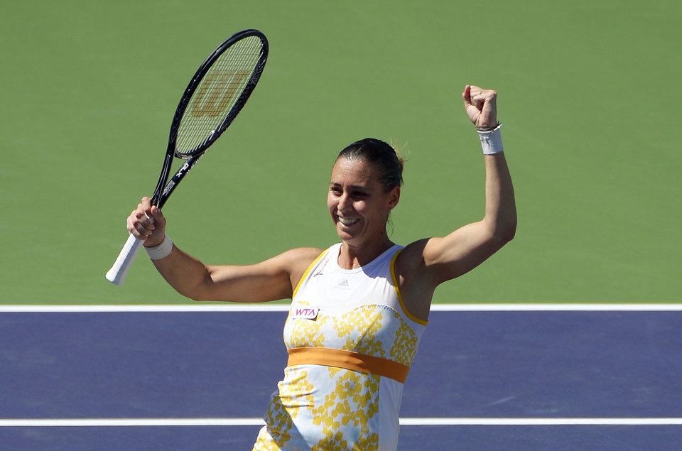 Photo - Flavia Pennetta, of Italy, raises her racquet after she beat Agnieszka Radwanska, of Poland, 6-2, 6-1, in the final round of the BNP Paribas Open tennis tournament, Sunday, March 16, 2014, in Indian Wells, Calif. (AP Photo/Mark J. Terrill)
