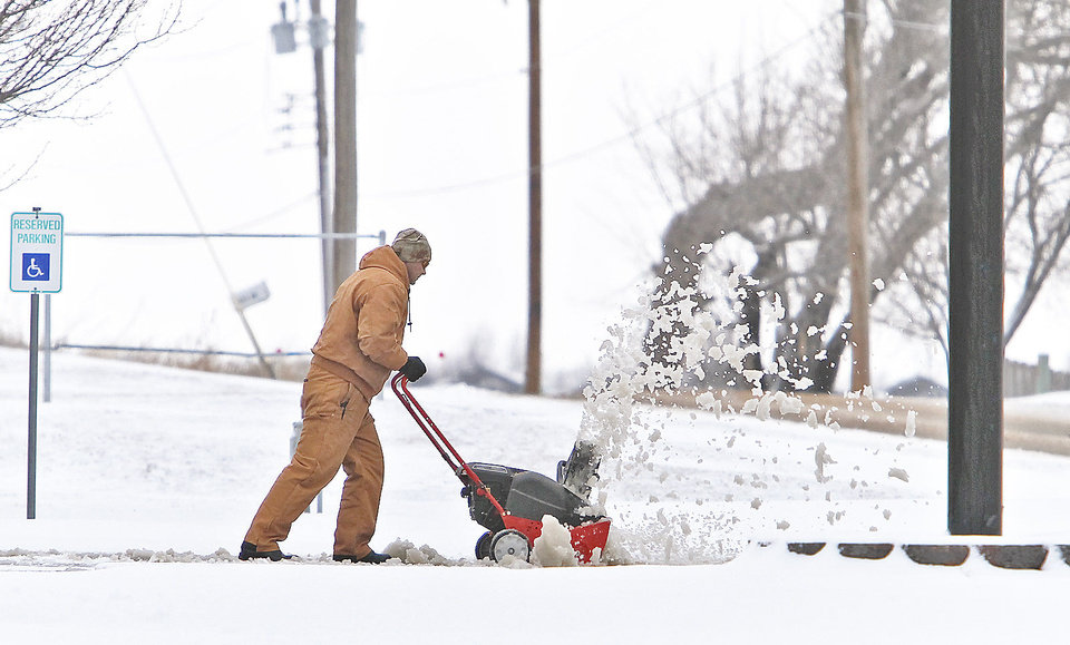 Photo - A business owner uses a snowblower Monday to clear a drive in Yukon.  Photo by Chris Landsberger, The Oklahoman