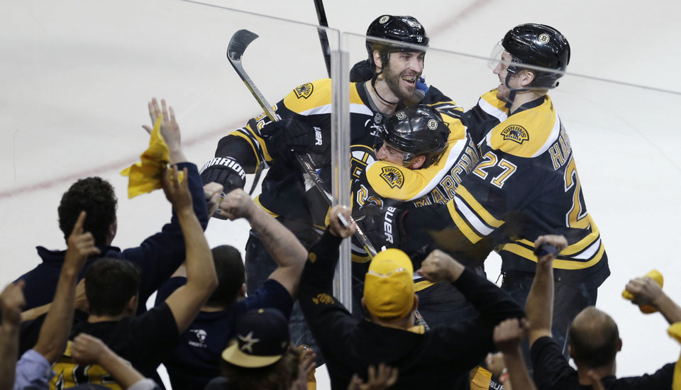 Photo - Boston Bruins left wing Brad Marchand, center, is congratulated by teammates Dougie Hamilton (27) and Zdeno Chara, left, following his game-winning goal against New York Rangers goalie Henrik Lundqvist during overtime in Game 1 of an NHL hockey playoffs Eastern Conference semifinal game in Boston, Thursday, May 16, 2013. The Bruins won 3-2. (AP Photo/Charles Krupa)